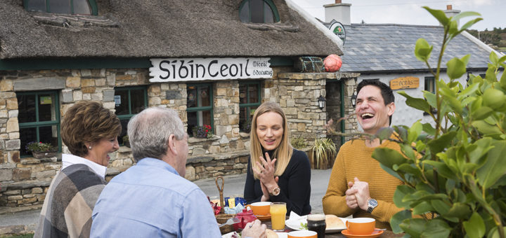 Book Direct & Save - Best Price Guarantee | Save up to 22% with Trident Holiday Homes | People sitting outside a pub in Clontallagh © Toursim Ireland